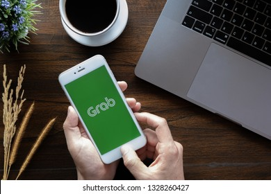 CHIANG MAI,THAILAND - January 20, 2019 : A MAN hand holding Grab app showing on iphone 6 with computer laptop and ear podon wood desk in coffee shop. Grab is smartphone app-based transportation networ