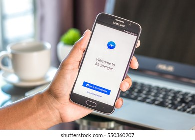Chiang Mai,Thailand - January 7, 2017 : Asian man holding Samsung Galaxy S6 with facebook messenger app on the screen on desk office. Top view of business workplace.