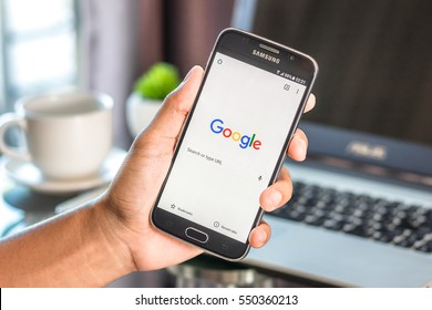 Chiang Mai,Thailand - January 7, 2017 : Asian man holding Samsung Galaxy S6 with google search app on the screen on desk office. Top view of business workplace.
