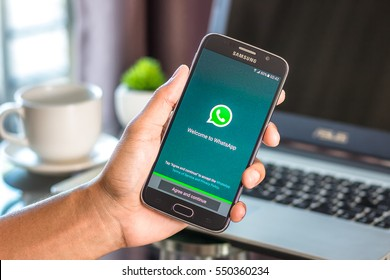 Chiang Mai,Thailand - January 7, 2017 : Asian man holding Samsung Galaxy S6 with whatsapp app on the screen on desk office. Top view of business workplace.