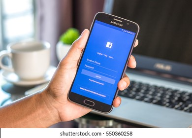 Chiang Mai,Thailand - January 7, 2017 : Asian man holding Samsung Galaxy S6 with facebook app on the screen on desk office. Top view of business workplace.