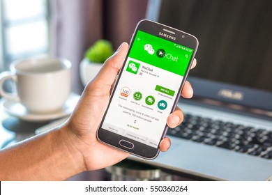 Chiang Mai,Thailand - January 7, 2017 : Asian man holding Samsung Galaxy S6 with wechat app on the screen on desk office. Top view of business workplace.
