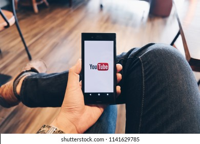 CHIANG MAI,THAILAND - July 07, 2018: A woman showing screen shot of Youtube on sony mobile phone YouTube app on the screen lying on old wood desk. YouTube is the popular online video sharing website.