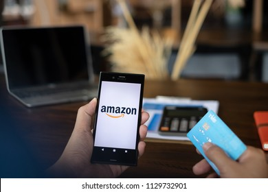CHIANG MAI,THAILAND - JULY 08, 2018 : Smartphone showing Amazon logo and credit card shopping online. Amazon.com, Inc. American international electronic commerce company.