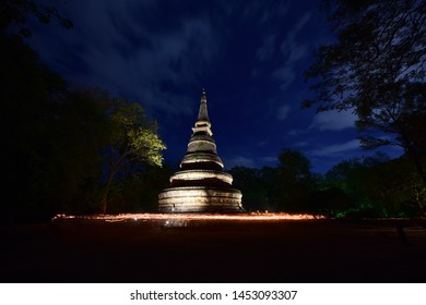 Chiang mai/Thailand - July 16 2019 : Thai Buddhists walking with lighted candles in hand around the  pagoda to celebrate Asalha Bucha at Wat U-Mong (U-Mong Temple)