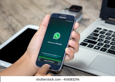CHIANG MAI,THAILAND - JULY 21, 2016 : Asian Woman holding Samsung Galaxy S6 with whatsapp app on the screen on Wood desk office. Top view of Business workplace.