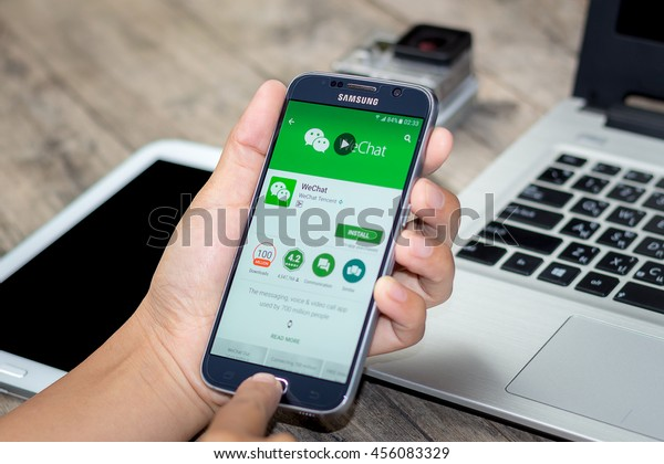 CHIANG MAI,THAILAND - JULY 21, 2016 : Asian Woman holding Samsung Galaxy S6 with wechat app on the screen on Wood desk office. Top view of Business workplace.
