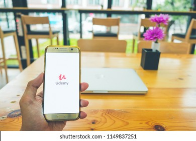 CHIANG MAI,THAILAND - July 28,2018: Man holds Mobile Phone using Udemy app on the screen with computer laptop on wooden table.