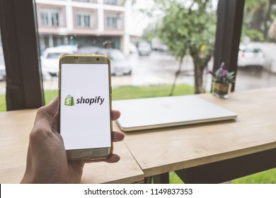 CHIANG MAI,THAILAND - July 28,2018: Man holds Mobile Phone using Shopify app on the screen with computer laptop on wooden table.