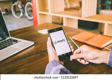 CHIANG MAI,THAILAND - July 7,2018: Man holds Mobile Phone using Shopify app on the screen with computer laptop on wooden table.