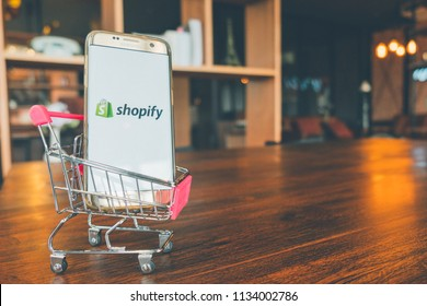 CHIANG MAI,THAILAND - July 7,2018: Mobile Phone using Shopify app on the screen in shopping cart on wooden table.