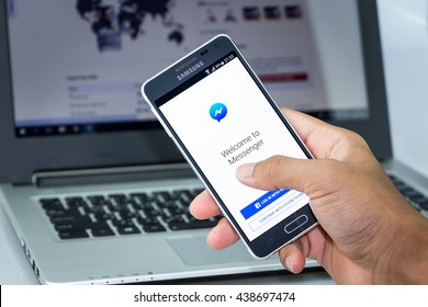 CHIANG MAI,THAILAND - JUN 18, 2016 : Man holding Samsung galaxy Alpha with facebook messenger app on the screen on desk office. Top view of Business workplace. Against the background of the computer.