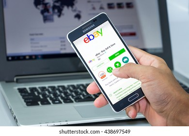 CHIANG MAI,THAILAND - JUN 18, 2016 : Man holding Samsung galaxy Alpha with ebay app on the screen on desk office. Top view of Business workplace. Against the background of the computer.