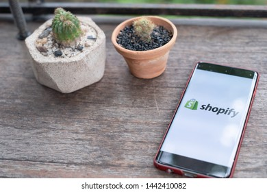 CHIANG MAI,THAILAND - June 29,2019: Shopify mobile application on smartphone screen, on wooden bar in coffee shop.