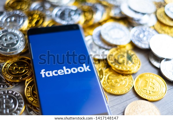 CHIANG MAI,THAILAND - JUNE 6,2019: facebook app on mobile phone screen and bitcoins coins , fb coins cryptocurrency concept.