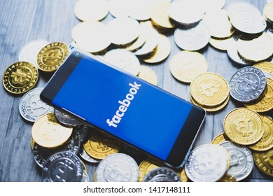 CHIANG MAI,THAILAND - JUNE 6,2019: fb coins new ico facebook app on smartphone screen and golden bitcoin coins on wooden floor.