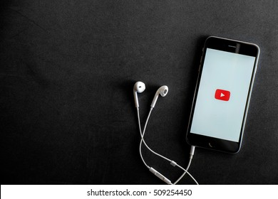 CHIANG MAI,THAILAND - NOV 03, 2016 : Apple iPhone 6 Plus with YouTube app on the screen lying on black desk with headphones. YouTube is the popular online video-sharing website,
