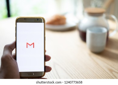 CHIANG MAI,THAILAND - Nov 14,2018: male hands holding smartphone using Gmail app on the screen at the coffee shop.