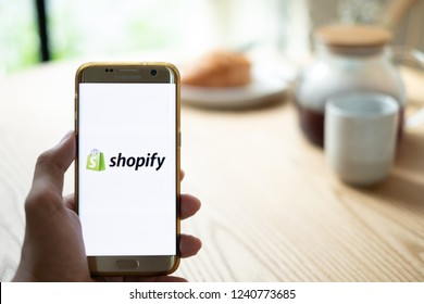 CHIANG MAI,THAILAND - Nov 14,2018: male hands holding smartphone using Shopify app on the screen at the coffee shop.