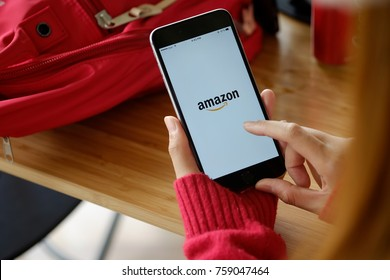 CHIANG MAI,THAILAND - NOV 18, 2017 : Woman holding iPhone 7 Plus showing Amazon apps. Amazon.com, Inc. is an American international electronic commerce company.