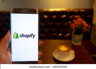 CHIANG MAI,THAILAND - Oct 14,2018: Hand Holding Mobile Phone using Shopify app on the screen with Cup of cappuccino coffee on wooden table