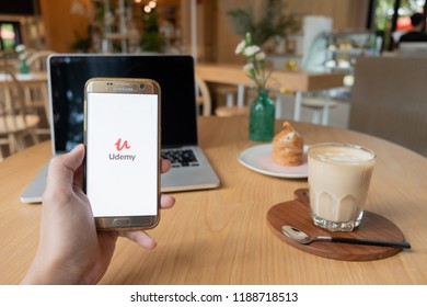CHIANG MAI,THAILAND - Sep 26,2018: Hand Holding Mobile Phone using Udemy app on the screen with notebook on wooden table in coffee shop.