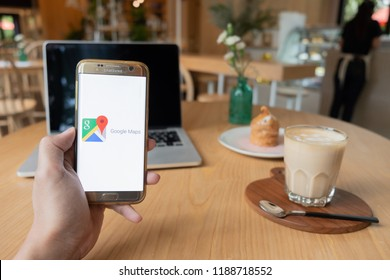 CHIANG MAI,THAILAND - Sep 26,2018: Hand Holding Mobile Phone using Google Map app on the screen with notebook on wooden table in coffee shop.