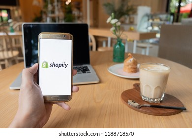 CHIANG MAI,THAILAND - Sep 26,2018: Hand Holding Mobile Phone using Shopify app on the screen with notebook on wooden table in coffee shop.