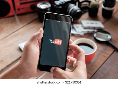 CHIANG MAI,THAILAND - SEP 29, 2015: Brand new Apple iPhone 6 plus with YouTube app on the screen lying on old wood desk with headphones. YouTube is the popular online video sharing website