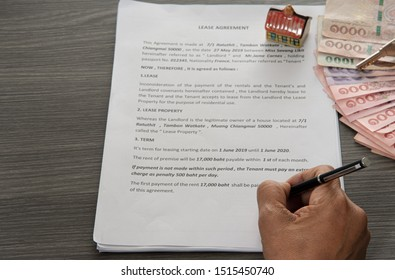 CHIANG MAI,THAILAND- SEPTEMBER 21,2019: Pen in hand signing house lease agreement with money and house key on wooden desk ,House rental concept on September 21,2019 in Chiang Mai, Thailand