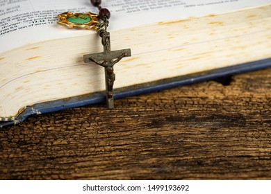 CHIANG MAI,THAILAND - SEPTEMBER 9,2019: Opened holy bible and Christian rosary beads on top main focus at Jesus Christ crucifix with wooden background on September 9,2019 in Chiang Mai, Thailand.