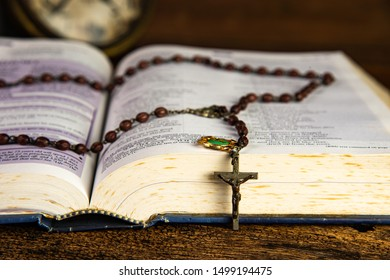 CHIANG MAI,THAILAND - SEPTEMBER 9,2019 : Opened holy bible and Christian rosary beads on top with blurred vintage alarm clock and wooden background on September 9,2019 in Chiang Mai, Thailand.