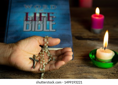 CHIANG MAI,THAILAND - SPETEMBER 9,2019 : Hand holding antique Jesus crucifix and rosary beads over holy bible and light candles on wooden background on September 9,2019 in Chiang Mai,Thailand.