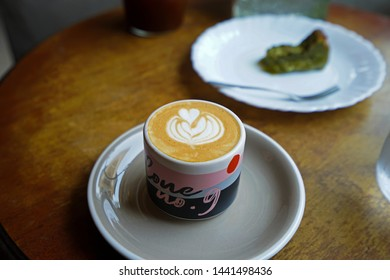 CHIANG MAI,THAILAND-APRIL 28,2019:A ceramic mug of hot Latte and Matcha green tea cake on wooden table at 'LOOPER AND CO' local coffee cafe and cocktail bar