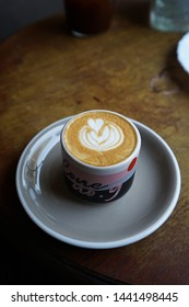 CHIANG MAI,THAILAND-APRIL 28,2019:A ceramic mug of hot Latte on wooden table at 'LOOPER AND CO' local coffee cafe and cocktail bar