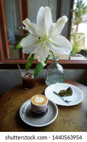 CHIANG MAI,THAILAND-APRIL 28,2019:Ceramic mug of hot Latte, Matcha green tea cake,a glass of iced black Americano on wooden table decorated with Lily 'LOOPER AND CO' local coffee cafe and cocktail bar
