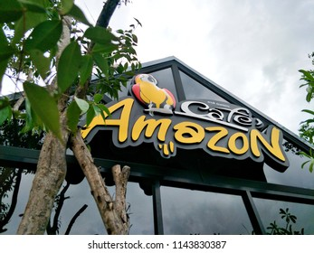 Chiang Mai,Thailand.July 28,2018.Close up logo of Cafe Amazon is beverage shop in PTT oil station with outdoor ornamental plants on foreground.