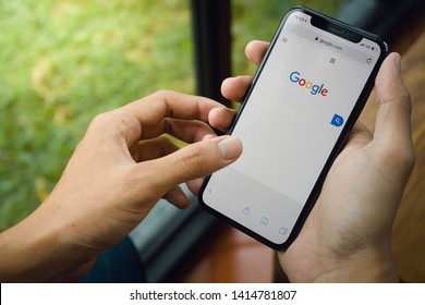 CHIANG MAI,THAILAND-JUN 4,2019 Close-up image of hands using smartphone search Google app on iPhone X is an online social networking is popular In year. - Image