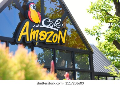 Chiang Mai,Thailand.June 21,2018.Close up logo of Cafe Amazon is beverage shop in PTT oil station with blurred outdoor ornamental plants on foreground.