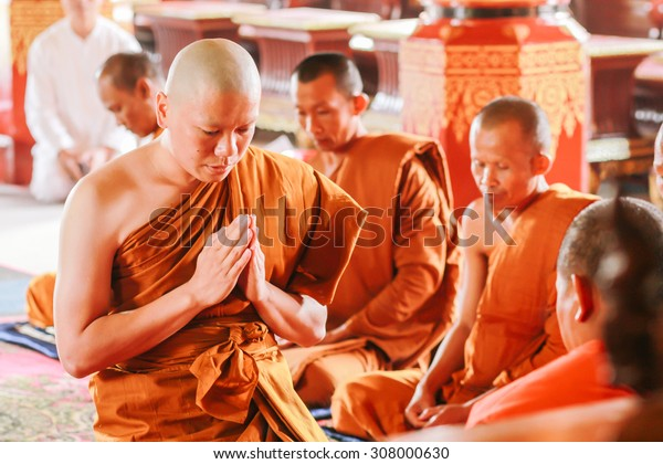 CHIANG RAI ,THAILAND-?July 18 : Newly ordained Buddhist monk pray with priest procession. Newly ordained Buddhist monks have a ritual in the temple procession in July ?18, ?2015