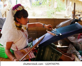 CHIANG RAI, THAILAND—MARCH 2018: A girl from the Long Neck Karen Hill tribe weaves a cloth from a traditional loom.