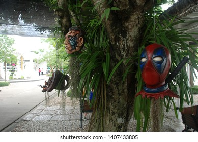 Chiang Rai, Thailand - 6/14/2018: Head of Deadpool and other movie characters hanging on a tree in a garden of Wat Rong Khun alias the White Temple