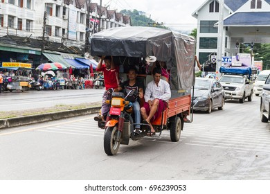 CHIANG RAI, THAILAND, AUG 8,2017: Myanmar man driving trucking motor-tricycle with plastic roof  on street in Measai,Chiang Rai,Thailandon on August 8, 2017.