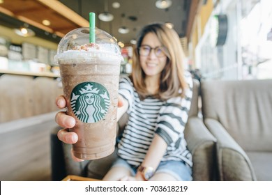 CHIANG RAI, THAILAND- August-27-2017 : Asian women holding a venti cup of frappuccino Granola dark mocha in Starbucks coffee shop.