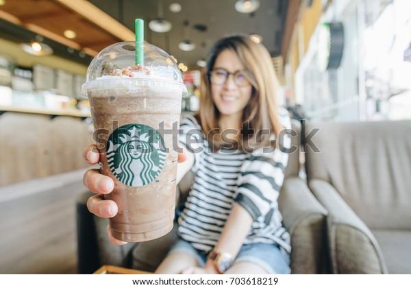 CHIANG RAI, THAILAND- August-27-2017 : Asian women holding a venti cup of frappuccino Granola dark mocha in Starbucks coffee shop.