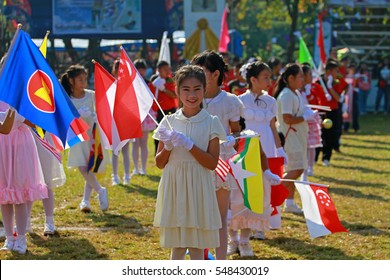 CHIANG RAI, THAILAND, DEC 21,2016: Girls hold and wave ASEAN flags in parade on sports Day in Chiang Rai on December 21, 2016.
