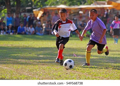 CHIANG RAI, THAILAND, DEC 22,2016: Young boy playing football in local compretition on sports Day in Chiang Rai on December 22, 2016.