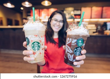 CHIANG RAI, THAILAND : December-26-2018 : Woman holding Starbucks Snowball peppermint dark mocha and Toffee nut crunch latte frappuccino in Starbucks coffee shop. The new 2018 designed holiday cup.
