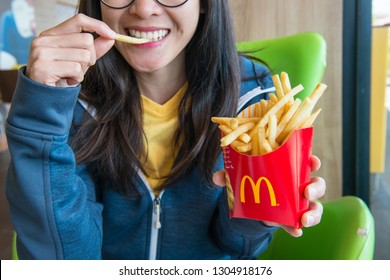 Chiang Rai, Thailand : February-05-2019 : Woman holding and eating french fries in McDonald's restaurant.