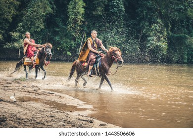 Chiang Rai, Thailand - Febuary 14, 2019 : Buddhist monks ride a horse and beg for food.